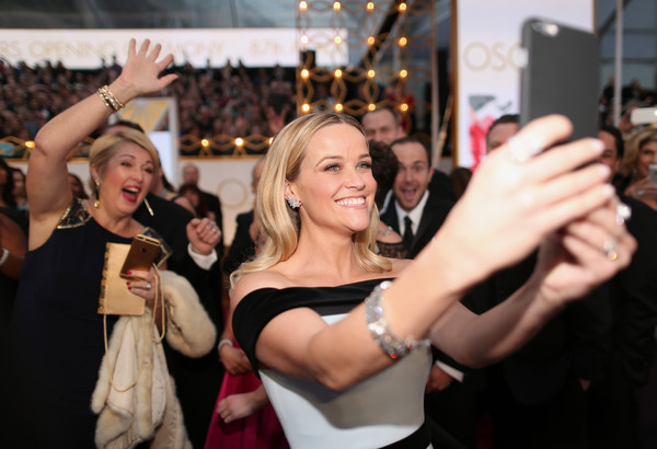 Actress Reese Witherspoon takes a selfie at the 87th Annual Academy Awards at Hollywood & Highland Center on February 22, 2015 in Hollywood, California.