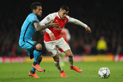 Dani Alves of Barcelona tackles Alexis Sanchez of Arsenal during the UEFA Champions League round of 16 first leg match between Arsenal and Barcelona on February 23, 2016 in London, United Kingdom.