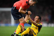 Santi Cazorla of Arsenal is helped to his feet by referee Danny Makkelie during the UEFA Champions League group A match between Arsenal FC and FC Basel 1893 at the Emirates Stadium on September 28, 2016 in London, England.