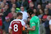 Petr Cech of Arsenal gives Aaron Ramsey the captains armband after being substitued for an injury during the Premier League match between Arsenal FC and Watford FC at Emirates Stadium on September 29, 2018 in London, United Kingdom.