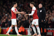 Mesut Ozil of Arsenal is substituted for Aaron Ramsey of Arsenal during the Premier League match between Arsenal FC and Leicester City at Emirates Stadium on October 22, 2018 in London, United Kingdom.