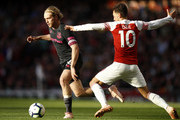 Tom Davies of Everton is challenged by Mesut Ozil of Arsenal during the Premier League match between Arsenal FC and Everton FC at Emirates Stadium on September 23, 2018 in London, United Kingdom.