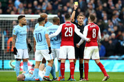 Aaron Ramsey of Arsenal is shown a yellow card by referee Craig Pawson during the Carabao Cup Final between Arsenal and Manchester City at Wembley Stadium on February 25, 2018 in London, England.