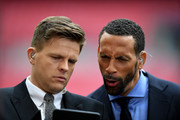 BT Sport presenter Jake Humphrey (L) and pundit Rio Ferdinand look at a smartphone prior to the Emirates FA Cup Semi-Final match between Arsenal and Manchester City at Wembley Stadium on April 23, 2017 in London, England.