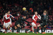 Aaron Ramsey of Arsenal gets to the ball ahead of Ilkay Gundogan and Kevin De Bruyne of Manchester City during the Premier League match between Arsenal and Manchester City at Emirates Stadium on March 1, 2018 in London, England.