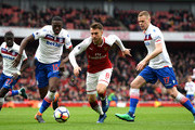 Aaron Ramsey of Arsenal gets away from Bruno Martins Indi of Stoke City and Ryan Shawcross of Stoke City during the Premier League match between Arsenal and Stoke City at Emirates Stadium on April 1, 2018 in London, England.