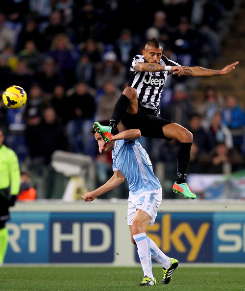 Arturo Vidal Cristian Ledesma (L) of S.S. Lazio competes for the ball with Arturo Vidal of Juventus during the Serie A match between S.S. Lazio and Juventus at Stadio Olimpico on January 25, 2014 in Rome, Italy.