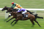 Hanoverian Baron and Kieren Fallon (orange) challenge between runners before winning The Newsmith Capital October Club Charity Handicap Stakes   at Ascot racecourse on July 23, 2010 in Ascot, England
