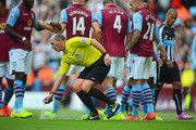 Referee Mike Dean uses vanishing spray to mark the Villa wall during the Barclays Premier League match between Aston Villa and Newcastle United at Villa Park on August 23, 2014 in Birmingham, England.