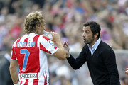 Head coach Enrique Sanchez Flores of Atletico Madrid gives instructions to Diego Forlan during the La Liga match between Atletico Madrid and Barcelona at Vicente Calderon Stadium on September 19, 2010 in Madrid, Spain.