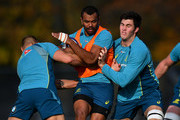 Kurtley Beale of Australia is tackled by Billy Meakes and Liam Wright of Australia during a training session at the Lensbury Hotel on November 16, 2017 in London, England.