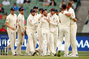 Jonny Bairstow and Stuart Broad of England celebrate after dismissing Shaun Marsh of Australia with Joe Root and their teammates during day one of the Fourth Test Match in the 2017/18 Ashes series between Australia and England at Melbourne Cricket Ground on December 30, 2017 in Melbourne, Australia.