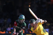 Michael Clarke of Australia cover drives with Maurice Ouma of Kenya looking on during the 2011 ICC World Cup Group A match between Australia and Kenya at M. Chinnaswamy Stadium on March 13, 2011 in Bangalore, India.