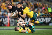 Liam Squire of the All Blacks is tackled by Bernard Foley and David Pocock of the Wallabies during The Rugby Championship Bledisloe Cup match between the Australian Wallabies and the New Zealand All Blacks at ANZ Stadium on August 18, 2018 in Sydney, Australia.