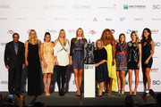 L-R Caroline Wozniacki of Denmark, Agnieszka Radwanska of Poland, Petra Kvitova of Czech Republic, Maria Sharapova of Russia,Stacy Allaster CEO and Chairman of the WTA, Serena Williams of the USA,Simona Halep of Romania, Eugenie Bouchard of Canada and Ana Ivanovic of Serbia pose for a group photograph at the Marina Bay Sands shopping centre afterthe draw ceremony prior to the start of the BNP Paribas WTA Finals at Singapore Sports Hub on October 18, 2014 in Singapore.