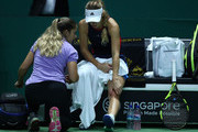 Caroline Wozniacki of Denmark receives treatment from WTA trainer Lindsey Ayala during a medical timeout in her singles match with Petra Kvitova of the Czech Republic prior to their singles match during day 3 of the BNP Paribas WTA Finals Singapore presented by SC Global at Singapore Sports Hub on October 23, 2018 in Singapore.  at Singapore Sports Hub on October 23, 2018 in Singapore.