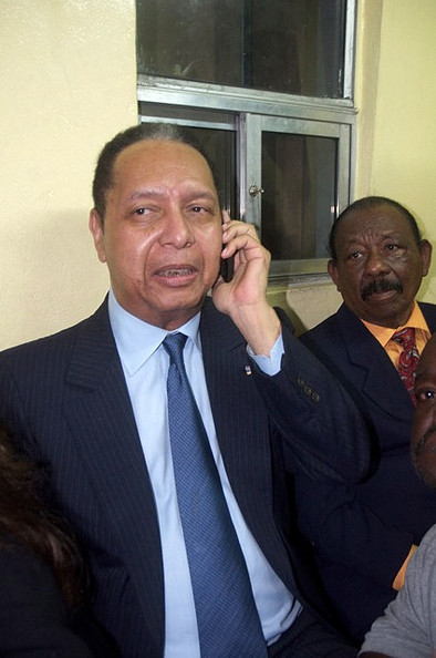"""Jean-Claude  Duvalier (C), the former Haitian leader """"Baby Doc"""", speaks on  his phone upon arriving at the airport on January 16, 2011 in  Port-au-Prince, Haiti. Duvalier was greeted by supporters upon returning  to his homeland for the first time in 25 years from his exile in  France."""