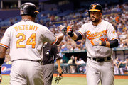 Outfielder Nick Markakis #21 of the Baltimore Orioles is congratulated by Wilson Betemit #24 after scoring against the Tampa Bay Rays during the game at Tropicana Field on August 4, 2012 in St. Petersburg, Florida.