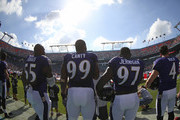 Baltimore Ravens players (L-R)Terrell Suggs #55, Chris Canty #99, Timmy Jernigan #97  and Sam Koch #4 walk to the field before the start of play against the Miami Dolphins in a game at Sun Life Stadium on December 7, 2014 in Miami Gardens, Florida.