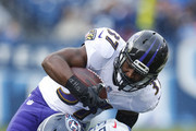 Javorius Allen #37 of the Baltimore Ravens is tackled by Daren Bates #53 of the Tennessee Titans during the first quarter at Nissan Stadium on October 14, 2018 in Nashville, Tennessee.