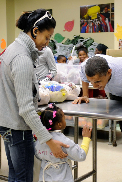 Barack Obama (AFP OUT) U.S. President Barack Obama talks with a young child as he packs and delivers bags of food to area residents ahead of the Thanksgiving Day holiday at Martha's Table on November 24, 2010 in Washington, DC.  The Obama family delivered turkeys and bags of food to needy families at Martha's Table, a 30-year-old non-profit that helps poor children, youth and families with food and clothing.