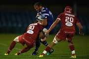 Jamie Roberts of Bath Rugby(C) is tackled by Rhys Patchell of Scarlets(L) during the Pre Season Friendly match between Bath and Scarlets at the Recreation Ground on August 24, 2018 in Bath, England.