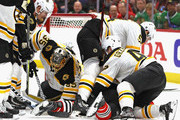 Anton Khudobin #35 of the Boston Bruins smothers the puck as teammates Adam McQuaid #54 and Matt Grzelcyk #48 pin Matthew Highmore #36 of the Chicago Blackhawks to the ice at the United Center on March 11, 2018 in Chicago, Illinois.