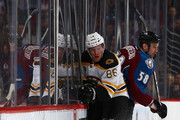Kevan Miller #86 of the Boston Bruins and Patrick Bordeleau #58 of the Colorado Avalanche collide with the boards during second period action at Pepsi Center on March 21, 2014 in Denver, Colorado.