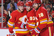 Juuso Valimaki #8 (L) of the Calgary Flames celebrates with Sam Bennett #93 and James Neal #18 after scoring against the Boston Bruins during an NHL game at Scotiabank Saddledome on October 17, 2018 in Calgary, Alberta, Canada.