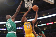 Dwight Howard #12 of the Los Angeles Lakers shoots over Kevin Garnett #5 and Paul Pierce #34 of the Boston Celtics at Staples Center on February 20, 2013 in Los Angeles, California.  NOTE TO USER: User expressly acknowledges and agrees that, by downloading and or using this photograph, User is consenting to the terms and conditions of the Getty Images License Agreement.
