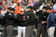 Manager Buck Showalter #26 of the Baltimore Orioles and manager Alex Cora #20 of the Boston Red Sox talk to the umpire crew before the game at Oriole Park at Camden Yards on June 11, 2018 in Baltimore, Maryland.