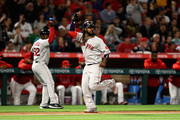 Hanley Ramirez #13 and Carlos Febles #52 signal a grandslam hit by Rafael Devers #11 of the Boston Red Sox during the third  inning of a game against the Los Angeles Angels of Anaheim  at Angel Stadium on April 18, 2018 in Anaheim, California.