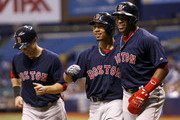 Mookie Betts #50 of the Boston Red Sox (C) celebrates his grand slam home run with teammates Daniel Nava #29 (L) and Yoenis Cespedes #52 during the second inning of a game against the Tampa Bay Rays on August 29, 2014 at Tropicana Field in St. Petersburg, Florida.