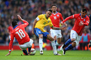 Neymar of Brazil is tackled by Gonzalo Jara (L) and Gary Medel (R) of Chile during the international friendly match between Brazil and Chile at the Emirates Stadium on March 29, 2015 in London, England.