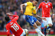 Neymar of Brazil is tackled by Gonzalo Jara of Chile during the international friendly match between Brazil and Chile at the Emirates Stadium on March 29, 2015 in London, England.