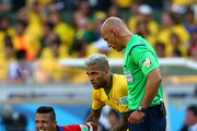 Alexis Sanchez of Chile reacts after a challenge as Dani Alves of Brazil and referee Howard Webb look on during the 2014 FIFA World Cup Brazil round of 16 match between Brazil and Chile at Estadio Mineirao on June 28, 2014 in Belo Horizonte, Brazil.