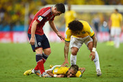 Neymar of Brazil lies on the field after a challenge as teammate Marcelo and James Rodriguez of Colombia look on during the 2014 FIFA World Cup Brazil Quarter Final match between Brazil and Colombia at Castelao on July 4, 2014 in Fortaleza, Brazil.