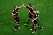 Andre Schuerrle of Germany (2nd R) celebrates scoring his team's sixth goal with Benedikt Hoewedes (L), Mesut Oezil (2nd L) and Thomas Mueller during the 2014 FIFA World Cup Brazil Semi Final match between Brazil and Germany at Estadio Mineirao on July 8, 2014 in Belo Horizonte, Brazil.
