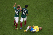 Neymar Jr of Brazil lies on the pitch injured while Andres Guardado and Carlos Vela of Mexico pass by during the 2018 FIFA World Cup Russia Round of 16 match between Brazil and Mexico at Samara Arena on July 2, 2018 in Samara, Russia.