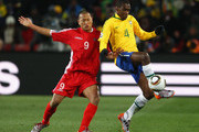 Jong Tae-Se of North Korea and Juan of Brazil battle for the ball during the 2010 FIFA World Cup South Africa Group G match between Brazil and North Korea at Ellis Park Stadium on June 15, 2010 in Johannesburg, South Africa.