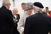 British Prime Minister Theresa May (C) chats with veteran William Bennett (R) following a service of remembrance at Bayeux cemetery on June 06, 2019 in Bayeux, France. Veterans and families gathered in Normandy to commemorate D-Day's 75th anniversary. It has been announced that 16 countries had signed a historic proclamation of peace to ensure the horrors of the Second World War are never repeated. The text has been agreed by Australia, Belgium, Canada, Czech Republic, Denmark, France, Germany, Greece, Luxembourg, Netherlands, Norway, New Zealand, Poland, Slovakia, the United Kingdom and the United States of America.