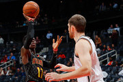 Dennis Schroder #17 of the Atlanta Hawks shoots against Tyler Zeller #44 of the Brooklyn Nets at Philips Arena on December 4, 2017 in Atlanta, Georgia.  NOTE TO USER: User expressly acknowledges and agrees that, by downloading and or using this photograph, User is consenting to the terms and conditions of the Getty Images License Agreement.