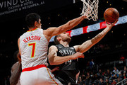 Tyler Zeller #44 of the Brooklyn Nets drives against Ersan Ilyasova #7 and Dewayne Dedmon #14 of the Atlanta Hawks at Philips Arena on January 12, 2018 in Atlanta, Georgia.  NOTE TO USER: User expressly acknowledges and agrees that, by downloading and or using this photograph, User is consenting to the terms and conditions of the Getty Images License Agreement.