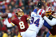 Quarterback Kirk Cousins #8 of the Washington Redskins passes the ball while teammate tackle Ty Nsekhe #79 blocks against defensive end Mario Williams #94 of the Buffalo Bills in the third quarter at FedExField on December 20, 2015 in Landover, Maryland.