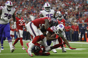 Chris Ivory #33 of the Buffalo Bills is tackled for a loss in the third quarter by Whitney Mercilus #59 of the Houston Texans and Zach Cunningham #41 at NRG Stadium on October 14, 2018 in Houston, Texas.