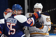 Johnny Boychuk #55 of the New York Islanders gets the stick up on Marcus Foligno #82 of the Buffalo Sabres during the second period at the Nassau Veterans Memorial Coliseum on April 4, 2015 in Uniondale, New York.