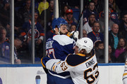 Brian Strait #37 of the New York Islanders and Tyler Ennis #63 of the Buffalo Sabres get tangled up during the first period at the Nassau Veterans Memorial Coliseum on April 4, 2015 in Uniondale, New York.