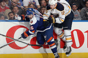 Cal Clutterbuck #15 of the New York Islanders is checked by Rasmus Ristolainen #55 of the Buffalo Sabres during the third period at the Nassau Veterans Memorial Coliseum on April 4, 2015 in Uniondale, New York.  The Islanders shut out the Sabres 3-0.