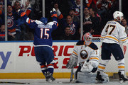 Cal Clutterbuck #15 of the New York Islanders celebrates a third period goal by Brock Nelson #29 (not shown) against Andrey Makarov #1 of the Buffalo Sabres at the Nassau Veterans Memorial Coliseum on April 4, 2015 in Uniondale, New York.  The Islanders shut out the Sabres 3-0.