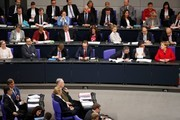 German Chancellor Angela Merkel (1st row R) talks with German Vice Chancellor and Foreign Minister Sigmar Gabriel (2ndR) and German Interior Minister Thomas de Maiziere (3rd R) as the  co-leaders of the parliamentary group of the Alternative for Germany (AfD) far-right party Alexander Gauland and Alice Weidel (C, foreground) sit during a session at the Bundestag lower house of Parliament, on November 21, 2017 in Berlin. / AFP PHOTO / Odd ANDERSEN